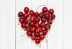 Röda körsbär i hjärta formar på vit träbakgrund Royaltyfri Foto