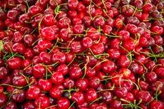 Röda körsbär med stjälk på gatamarknad royaltyfri foto