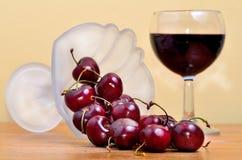 Röda körsbär och vin arkivfoton