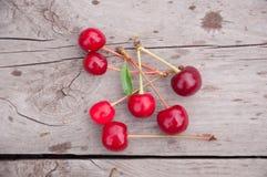 Röda körsbär på trä Arkivfoton