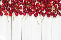 Röda körsbär på vit träbakgrund Arkivbild