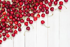 Röda körsbär på vit träbakgrund Arkivfoto
