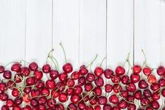 Röda körsbär på vit träbakgrund Fotografering för Bildbyråer