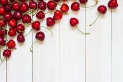 Röda körsbär på vit träbakgrund Royaltyfria Foton