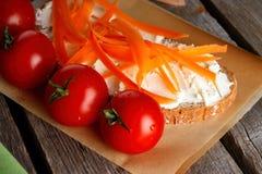 Röda körsbärsröda tomater framme av bröd med stugan Royaltyfria Foton