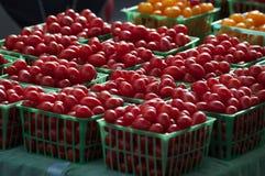 Röda körsbärsröda tomater i spjällådor på bönder marknadsför Arkivbilder