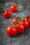 Röda körsbärsröda tomater i vattendroppar Royaltyfri Bild