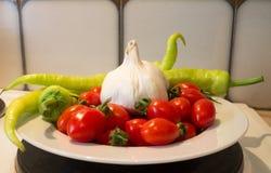Röda körsbärsröda tomater med varma peppar och vitlök fotografering för bildbyråer