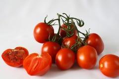 Röda körsbärsröda tomater, salt svart Arkivfoton