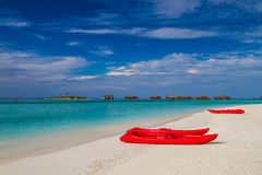 Röda kajaker i den vita sandiga stranden i Maldiverna royaltyfria bilder