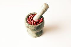 Röda kapslar och orange preventivpillerar med mortelmortelstötar på vit bakgrund Arkivfoton