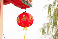 Röda kinesiska lyktor som hänger på takfoten Arkivbild