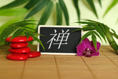 Röda kiselstenar som är ordnade i Zenlivsstil med en orkidé, en tänd stearinljus, en bambufilial och lövverk med meddelandezenen  Royaltyfri Fotografi