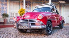 Röda klassiska Chevy parkeras framme av ett hem Fotografering för Bildbyråer