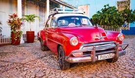 Röda klassiska Chevy parkeras framme av ett hem Royaltyfria Bilder