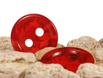 Röda knappar bland stenar Arkivbilder