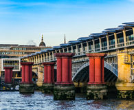 Röda kolonner i vattnet mot bakgrunden av en bro i L Arkivbilder