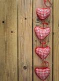 Röda kontrollhjärtor på lantlig träbakgrund Royaltyfri Fotografi