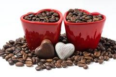 röda koppar med kaffebönor och chokladgodisar royaltyfri fotografi