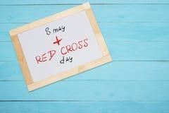 Röda korsetdag som märker på det vita skrivbordet, blå bakgrund Arkivfoto