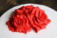 Röda kräm- sockerblommor på en vit fondant bakar ihop royaltyfri bild