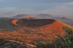 Röda krater av Mauna Kea på solnedgången royaltyfria bilder