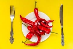 Röda kryddiga chilipeppar på guling Royaltyfria Foton