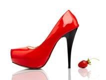 Röda kvinnors skor och jordgubbe Arkivbild