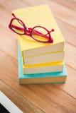 Röda läs- exponeringsglas på bunt av böcker Royaltyfri Fotografi