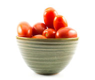 Röda långa tomater i en grön kopp på en vit bakgrund Arkivfoton