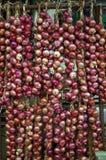 Röda lökar på en marknad för ny jordbruksprodukter. Arkivbild