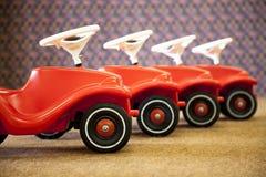 4 röda leksakbilar i rad Arkivbilder