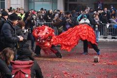 Röda Lion Dancing på de spenderade brandsmällarna Royaltyfri Bild