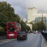 Röda London bussar under rusningstiden i centrala London som tar passagerare till och från arbete och shoppar korsa en askförenin Arkivfoto