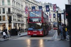 Röda London bussar under rusningstiden i centrala London som tar passagerare till och från arbete och shoppar korsa en askförenin Fotografering för Bildbyråer