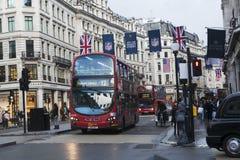 Röda London bussar under rusningstiden i centrala London som tar passagerare till och från arbete och shoppar korsa en askförenin Arkivbild