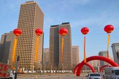 Röda lyktor och moderna byggnader Arkivbild