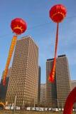 Röda lyktor och moderna byggnader Arkivfoto