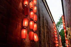 Röda lyktor tänd utvändig byggnad i gränd Arkivbild