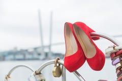 Röda lyxiga skor som hänger på staketet med lås av hjärtor mot himlen royaltyfria bilder