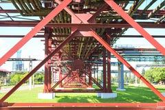 Röda metallstrukturer, hjulservice för rör, rörledningbock från stora strålar, högar och styvningsmedel på oljeraffinaderiet arkivfoton
