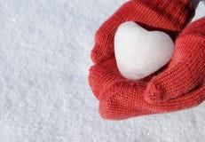 Röda mittens med snowhjärta Arkivfoto