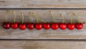 Röda mogna körsbär på träbakgrund Arkivfoto