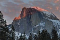 Röda moln över den halva kupolen på solnedgången, Yosemite nationalpark Royaltyfri Foto
