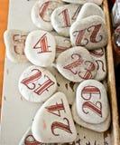 Röda nummer som dras på vita stenar Arkivfoto