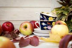 Röda nya äpplen med sidor och koppar för te Arkivfoton