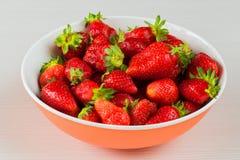 Röda nya jordgubbar i en bunke som isoleras på vit bakgrund Slapp fokus Arkivfoto