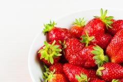 Röda nya jordgubbar i en bunke som isoleras på vit bakgrund Slapp fokus Fotografering för Bildbyråer