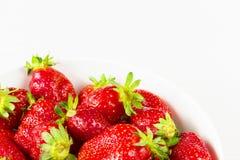 Röda nya jordgubbar i en bunke som isoleras på vit bakgrund Slapp fokus Arkivfoton