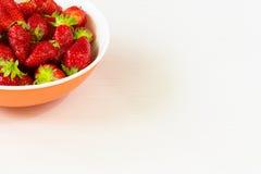 Röda nya jordgubbar i en bunke som isoleras på vit bakgrund Slapp fokus Arkivbild